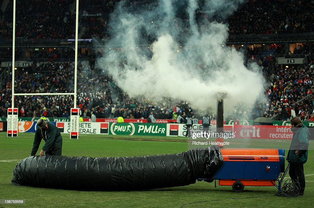 The groundsmen try to warm the pitch up with a heater before the match is called off just before kick off during the RBS 6 Nations match between France and Ireland at Stade de France on February 11, 2012 in Paris, France.