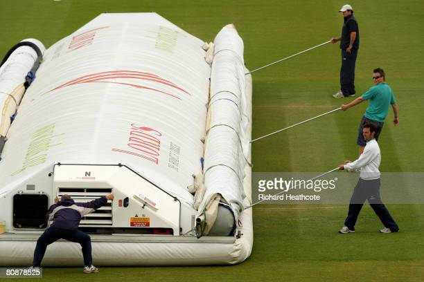 The groundstaff bring on the hover to cover the pitch as rain stops play during the Friends Provident Trophy match between Middlesex Crusaders and...