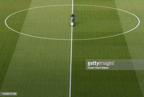 The groundstaff work on the Emirates Stadium pitch before the Premier League match between Arsenal and West Ham United on August 25 2018 in London...