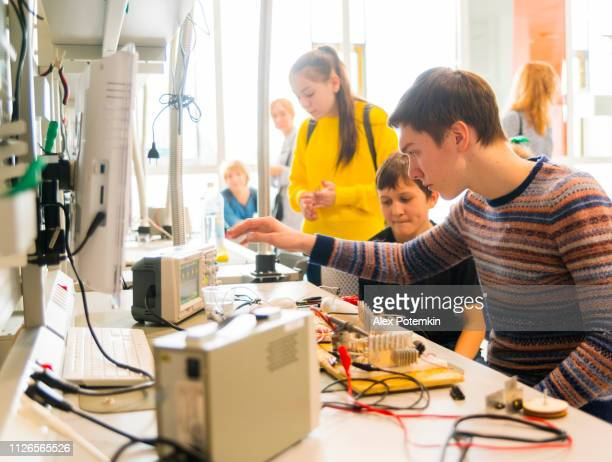 The group of kids of different ages, boys, and girls, working in the engineering laboratory