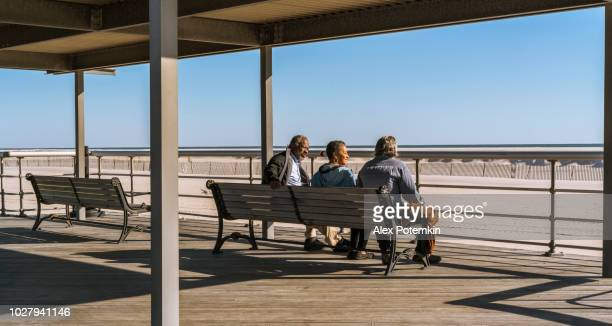 The group of senior friends resting and talking when they are sitting on thye bench on the waterfront