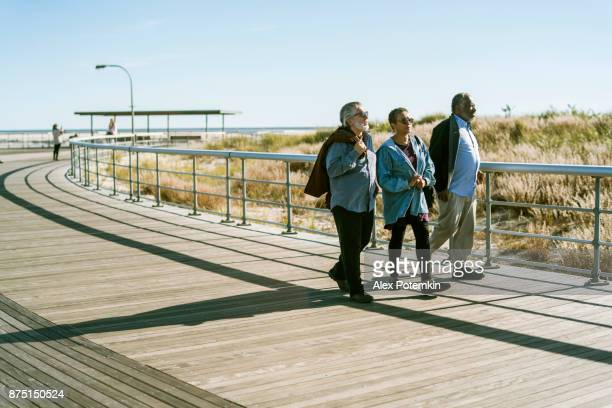 the group of senior friends walking on the beach - long island stock pictures, royalty-free photos & images