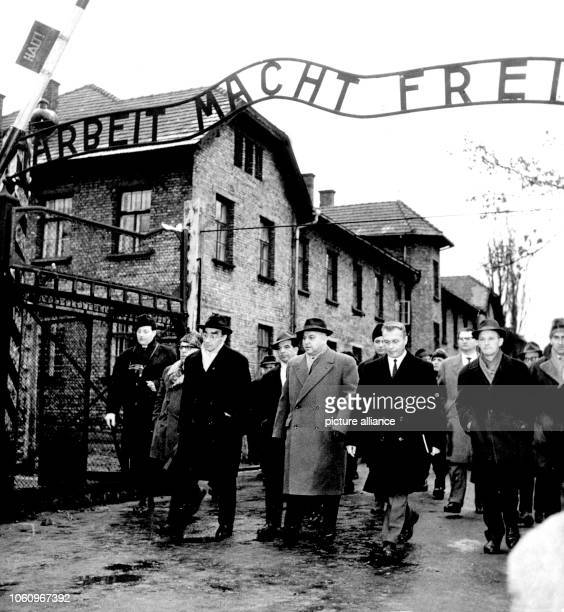 The group of the Frankfurt jury court and several journalists are passing the camp gate with the words 'Arbeit macht frei' . The first local...