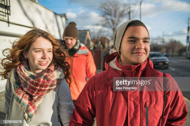 The group of young friends, include the inter-racial couple of Black beautiful woman and Caucasian white handsome man and teenagers, walking on the street