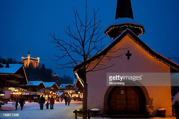 The Gstaad Palace luxury hotel left stands illuminated on a hill as pedestrians stroll along the promenade during the evening in Gstaad Switzerland...
