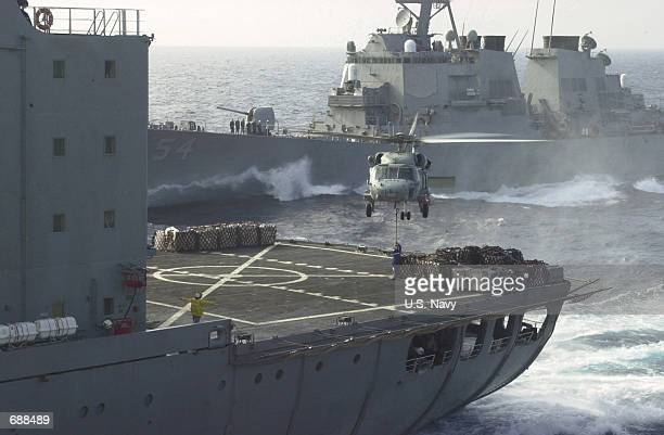 """The Guided missile destroyer USS Curtis Wilbur sails alongside the auxiliary fleet oiler USNS Walter S. Diehl as an SH-60E """"Seahawk"""" helicopter..."""