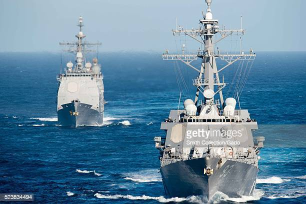 The guidedmissile destroyer USS Chung Hoon DDG 93 front and the guidedmissile cruiser USS Mobile Bay CG 53 take part in a show of force demonstration...