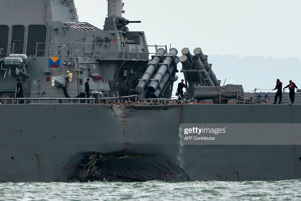 The guided-missile destroyer USS John S. McCain is seen with a hole on its portside after a collision with an oil tanker outside Changi naval base in Singapore on August 21, 2017. Ten US sailors were missing and five injured after their destroyer collided with a tanker east of Singapore early on August 21, the second accident involving an American warship in two months. / AFP PHOTO / Roslan RAHMAN