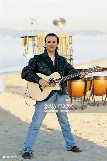 The guitarist Dodi Battaglia , member of the Italian band Pooh, posing with a guitar during a photo shoot on a beach. Rimini , 1995