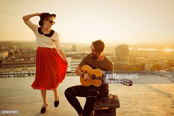 the guitarist playing and the woman dancing