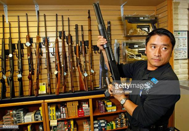 The Gun Store rangemaster Heu Thao shows a customer a shotgun November 14 2008 in Las Vegas Nevada Store manager Cliff Wilson said he's seen a large...