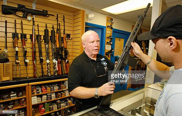 The Gun Store sales associate Michael Rogers shows Won Kim of Nevada a rifle November 14 2008 in Las Vegas Nevada Store manager Cliff Wilson said...
