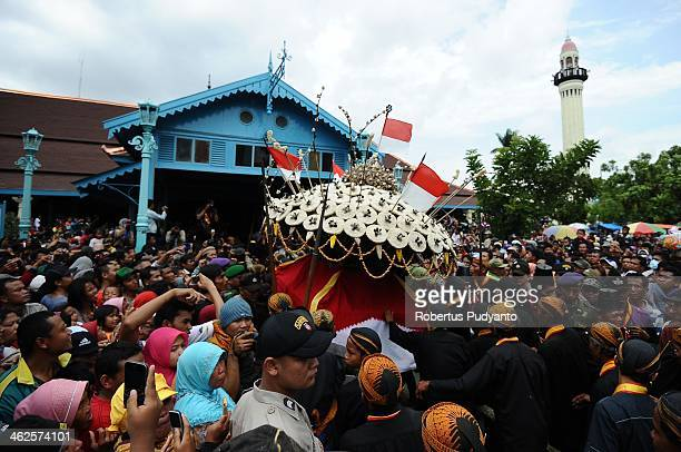 The Gunungan offering is paraded from Kemandungan Palace to Surakarta Grand Mosque during Grebeg Maulud on January 14 2014 in Solo City Indonesia...