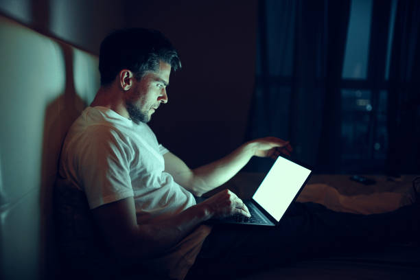 The guy at night use a laptop in his bed.