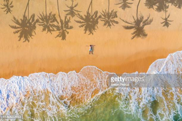 the guy lies on a sandy beach on a tropical island. drone view - strand stockfoto's en -beelden