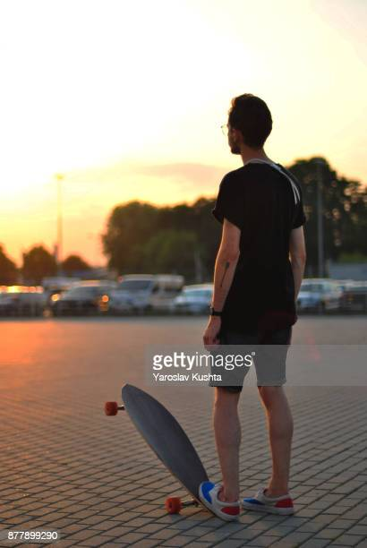 The guy makes a trick on the longboard