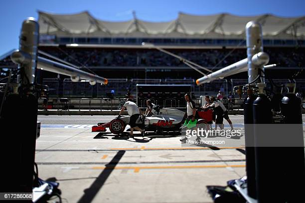 The Haas F1 team push the car of Romain Grosjean of France and Haas F1 down the pitlane during qualifying for the United States Formula One Grand...