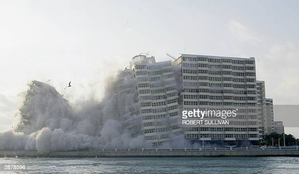 The Habour House is seen across Haulover inlet as 660 pounds of explosives bring it down 18 January 2004 in Miami Beach FL The building was...
