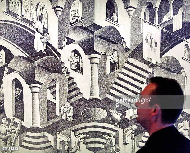 TO GO WITH AFP STORY 'SCIENCEARTMATHEMATICS' A man looks 14 November 2002 at Dutch artist MC Escher's artwork 'Hol en Bol' made in 1955 displayed at...