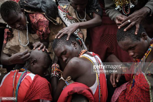 The hair of circumcised Maasai young men are shaved by their mother after coming out from the bush near Kilgoris Kenya on the last day of the annual...