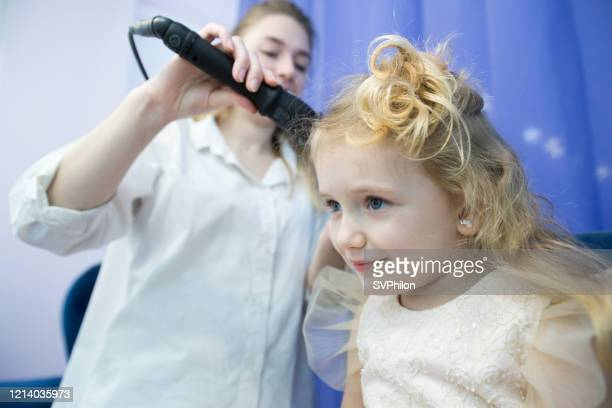 the hairdresser curls baby hair with a curling iron. - beauty salon ukraine stock pictures, royalty-free photos & images