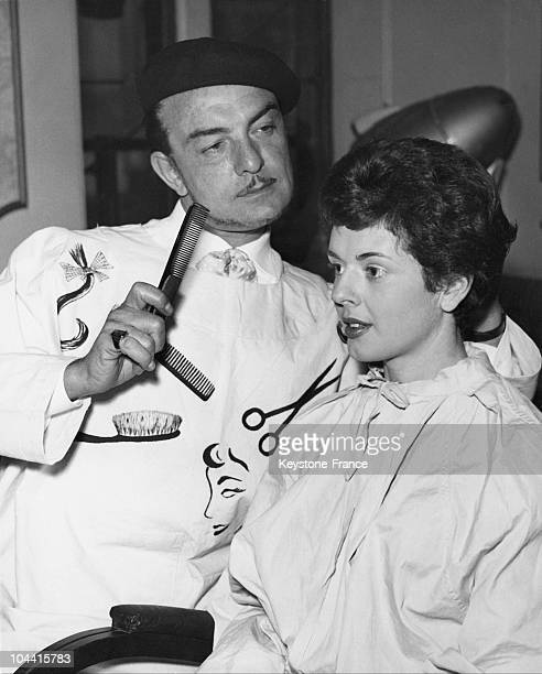 The hairdresser RAYMOND concentrating on the cut of his customer Deirdre ROSSITER
