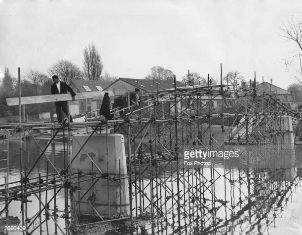 The halfbuilt pedestrian bridge connecting Eel Pie Island to the Middlesex mainland at Twickenham Surrey After completion a toll of one old penny to...