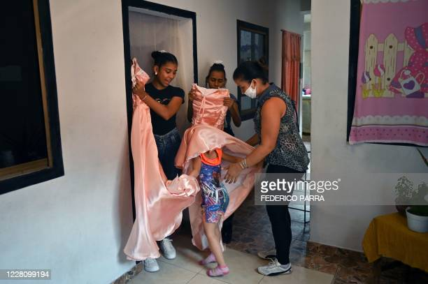 The halfsister of Eikalin Gonzalez and Sidneidy Uray , plays with the dresses her mother Ildemira Valera and her twin sister wore for the celebration...