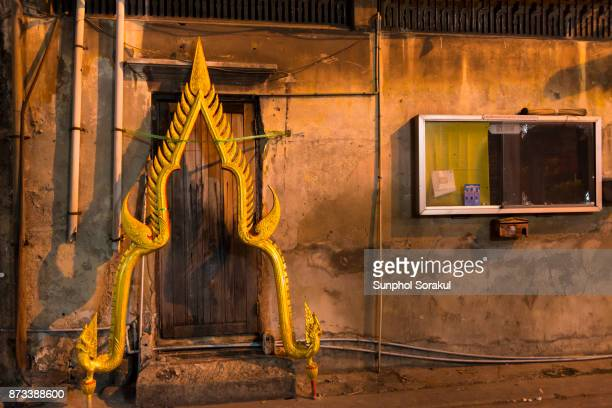 The halo of a Buddha statue leans against a door