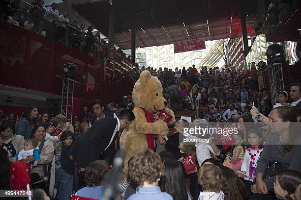 The Hamleys Plc bear mascot hugs a child at the opening of the company's new toy store at the Antara Mall in Mexico City Mexico on Monday Nov 30 2015...
