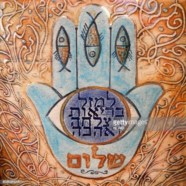 the hamsa, with fishes and blessings in hebrew - hand of fatima stock photos and pictures