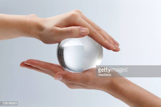 The hand holding the crystal ball