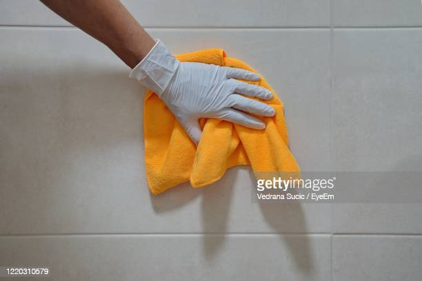 the hand in a white glove with wipe cloth washes a tiles - washing up glove stock pictures, royalty-free photos & images