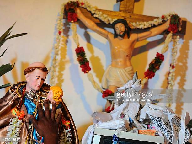 The hand of a Catholic devotee is pictured over religious idols during the annual pilgrimage at Saint Anthony's Church on Katchchativu Island in the...