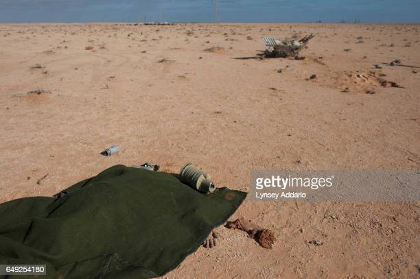 The hand of a dead pilot lies among the wreckage of a plane belonging to Muammar alGaddafi's Air force east of Ras Lanuf Libya Sunday March 6 2011...