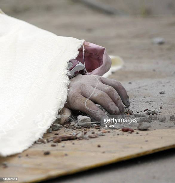 The hand of a dead young girl is covered by a sheet after being dugged out from the rubble of a collapsed elementary school in Yingxiu of Wenchuan...