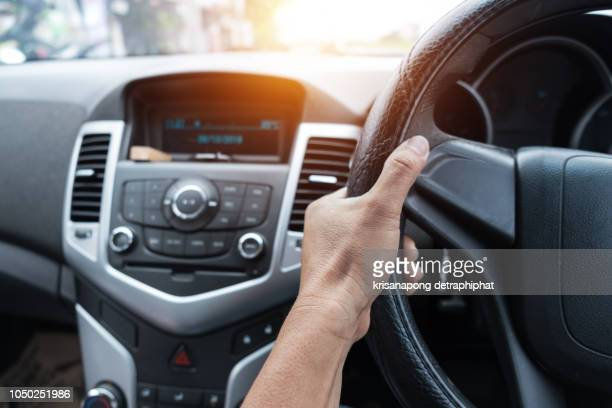 the hand of a man holding a steering wheel in the car. - steering wheel stock pictures, royalty-free photos & images