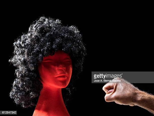 The hand of a man trying to punch, making gestures of harassment and ill-treatment of a woman