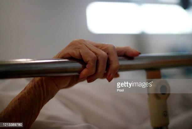 The hand of a patient grips the rail of a hospital bed in the Xray department at The Royal Blackburn Teaching Hospital in East Lancashire during the...