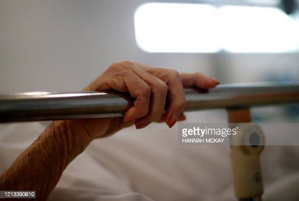 The hand of a patient grips the rail of a hospital bed in the X-ray department at the Royal Blackburn Teaching Hospital in Blackburn, north-west...