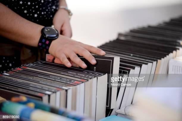 The hand of a person who is taking a book during Portici di Carta Portici di Carta is an annual event where 128 book sellers are placed in the Turin...