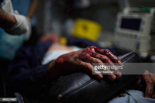 The hand of a severelyinjured motorbike accident victim rests on his bag in an ambulance on December 6 2014 in Vientiane Laos Vientiane Rescue is an...