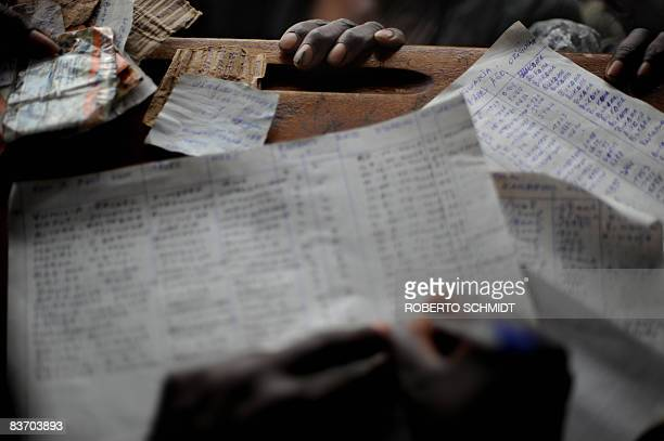 The hand of a woman displaced by violence in the North Kivu region of the Democratic Republic of Congo grips the table near papers to register their...