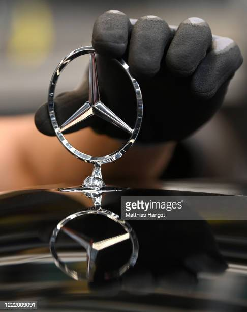 The hand of a worker seen with the 'Mercedes Stern' at the Mercedes-Benz factory following the resumption of automobile production this week during...