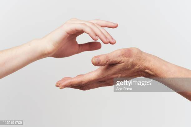 the hand of a young woman and an elderly woman - medical condition stock pictures, royalty-free photos & images