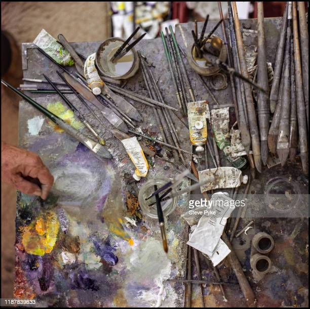 The hand of British landscape painter, Fred Cuming , mixing paint at his studio, Rye, East Sussex, 7th March 2000.