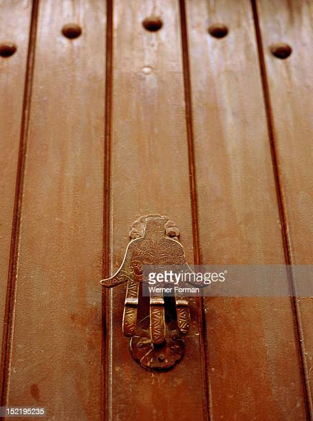 The hand of Fatima as the doorknocker for a house in the old city of Fez The hand is an ancient symbol of good luck and protection against the evil...