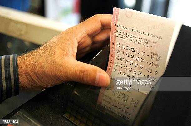 The hand of Sukhjit S Toor reaches for printed Mega Millions lottery tickets at a gas station which is located on the border of the state of...