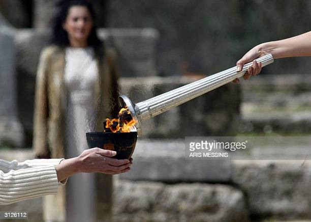 The hand of the high priestess is seen giving the Olympic flame to another priestess 24 March 2004 during a dress rehearsal ceremony for the Olympic...