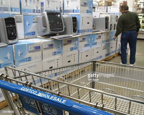 The handle of a Costco shopping cart is visible in an aisle as a customer shops in the computer department of a Costco Wholesale store March 8 2002...